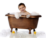 Happy Bubble Bath. A happy preschooler playing in a copper, claw-foot bathtub filled with bubbles.  Isolated on white Royalty Free Stock Images