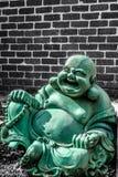 Happy Buddha. Against a brick wall stock photo