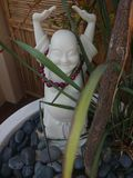 Happy Buddha. Fronds in front of a happy little Buddha royalty free stock photos
