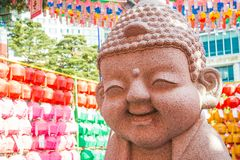 Happy Buddha with Laterns. A statue of a smiling, happy Buddha with colorful lanterns in the background royalty free stock photography