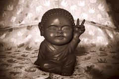 Happy buddha in sepia tone. May 12 2017. Alexandra. A sepia toned statue of a smiling happy Buddha with a peace sign on a silk elephant background royalty free stock image