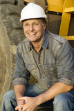 Happy builder. A portrait of a happy smiling construction worker sitting on steps of his digger Royalty Free Stock Photography