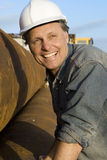 Happy builder. A portrait of a happy smiling construction worker leaning against large metal pipes Royalty Free Stock Images