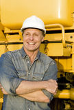 Happy builder. A portrait of a happy smiling construction worker leaning against his digger Royalty Free Stock Photo