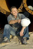 Happy builder. A portrait of a happy smiling construction worker leaning against large metal pipes Royalty Free Stock Photography