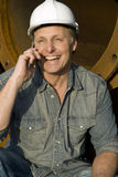 Happy builder on cellphone. A smiling construction worker is having a fun chat on his cellphone Stock Photography