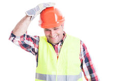 Happy builder holding hand on helmet. Acting funny isolated on white studio background Stock Photography