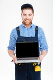 Happy builder in overall and cap holding blank screen laptop Royalty Free Stock Photography