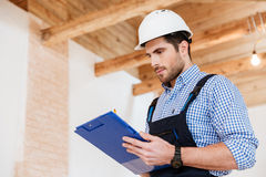 Happy builder writing notes in hardhat with clipboard Stock Photos