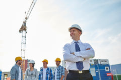 Happy builders and architect at construction site. Business, building, teamwork and people concept - group of smiling builders and architect in hardhats at Stock Photo