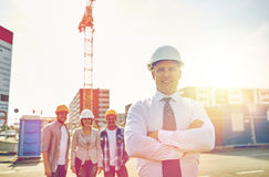 Happy builders and architect at construction site Royalty Free Stock Photo