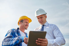 Happy builders in hardhats with tablet pc outdoors Stock Photography