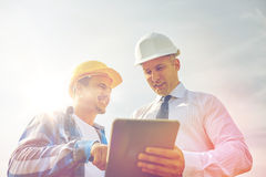 Happy builders in hardhats with tablet pc outdoors. Business, building, teamwork, technology and people concept - smiling builders in hardhats with tablet pc Royalty Free Stock Photo