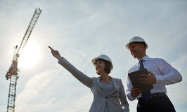 Happy builders in hardhats with tablet pc outdoors Royalty Free Stock Image