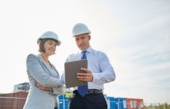 Happy builders in hardhats with tablet pc outdoors Royalty Free Stock Photography