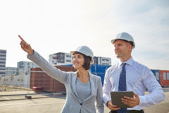 Happy builders in hardhats with tablet pc outdoors Stock Image