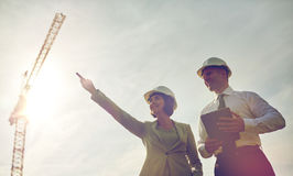 Happy builders in hardhats with tablet pc outdoors Stock Photo