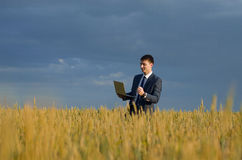 Happy buisnessmen in a wheat field. Happy farmer, businessman, standing in wheat field over wind turbines background with computer laptop Royalty Free Stock Photo