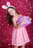 Happy bunny girl with gift boxes. Cute little happy girl is wearing pink dress and bunny ears on red background with snow is holding gift boxes Stock Image