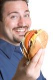 Happy Burger Man. Happy young man eating burger stock photo