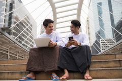 Happy Burmese businessmen in town. Handsome happy Burmese or Myanmar businessmen with longyi traditional dress working in Modern city. Fintech Foreign Business Stock Photography