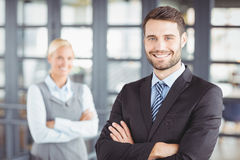 Happy businesman with female colleague in background Royalty Free Stock Images
