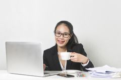 Asian woman working with laptop at white working table, diligent professional working woman drinking coffee while working on lapto. Happy business Asian woman stock photography