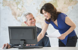 Happy Business Colleagues Discussing At Office Desk Stock Photo