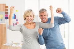 Happy business colleagues gesturing victory. Portrait of business colleagues gesturing victory at the office Stock Photography