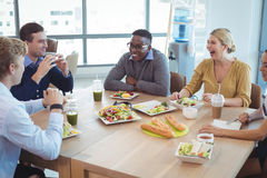 Happy business colleagues having lunch at office cafeteria. Happy business colleagues having lunch on table at office cafeteria stock photo