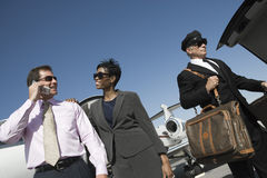 Happy Business Couple At Airfield. Low angle view of happy multiethnic business couple standing with driver holding luggage at airfield Stock Photography