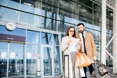 Business couple near the airport. Happy business couple in coats stading with tickets in front of the airport entrance Stock Images