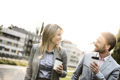 Happy business couple conversing while holding disposable cups in city Stock Photos