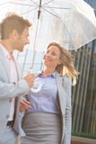 Happy business couple conversing under umbrella outdoors Stock Photo