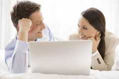 Happy business couple with laptop looking at each other in hotel Royalty Free Stock Photo
