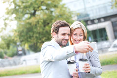 Happy business couple taking selfie while holding disposable cups in city Stock Photos
