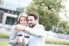 Happy business couple taking selfie while holding disposable cups in city Royalty Free Stock Photo