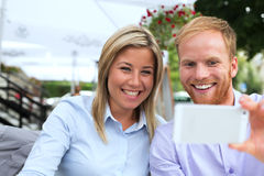 Happy business couple taking selfie at outdoor restaurant Royalty Free Stock Image