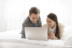 Happy business couple using laptop in hotel room Royalty Free Stock Photography