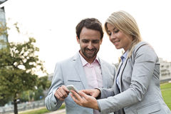 Happy business couple using smart phone at park Royalty Free Stock Image