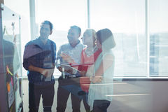 Happy business entrepreneurs looking at whiteboard seen through glass. At office royalty free stock photos