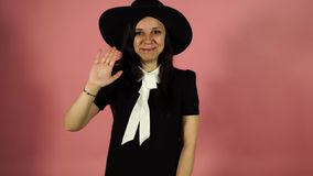 Happy business woman waving her hand on pink background. Lady looking at the camera in the Studio. The concept of. Happy business female waving her hand on pink stock video