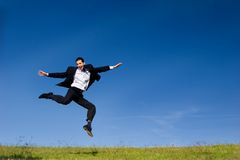 Happy business jump. Young buisnessman jumping on the meadow royalty free stock photography