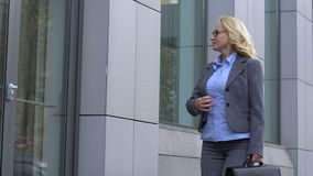 Happy business lady walking near office building, satisfied with loving job stock video footage