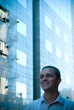 Happy business man. Young and happy business man in casual dress standing in front of an office building stock photography