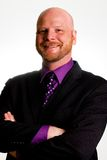 Happy Business Man. A handsome bald man wearing a suit with a purple shirt Stock Image