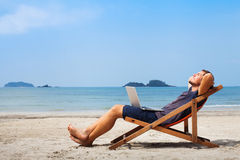Happy business man on the beach. Happy business man with laptop relaxing on the beach
