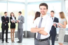 Happy business man with colleagues at the back. Handsome happy business man with colleagues at the back Royalty Free Stock Photos