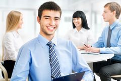 Happy business man with colleagues. Handsome happy business men with colleagues at the back Stock Images