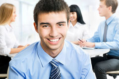 Happy business man with colleagues. Handsome happy business men with colleagues at the back Stock Photography